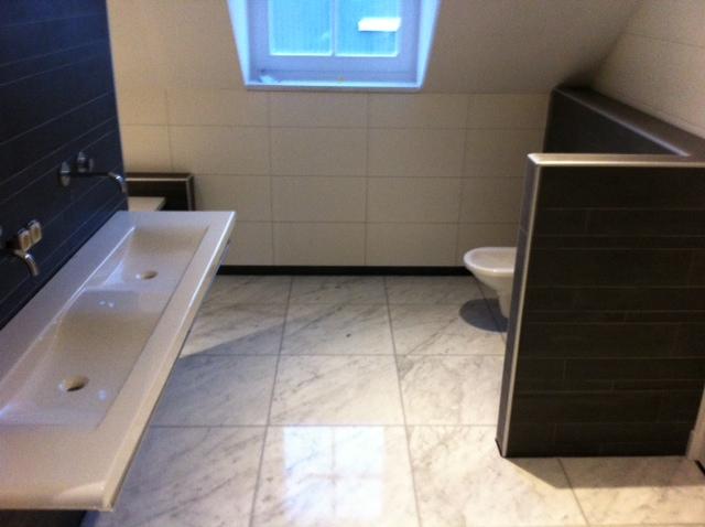 Badkamer in de kleuren zwart en wit. Grote witte tegels op de wand, afgewisseld met stroken en een marmeren vloer.